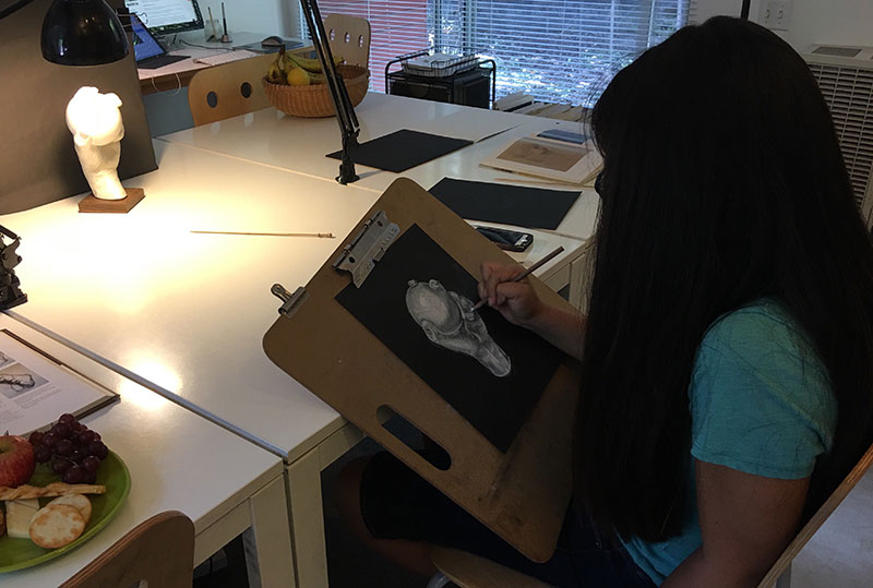 On Saturday, Level 3 youth student, Nicole, experimented with white pastel and charcoal to form the hand and sphere.