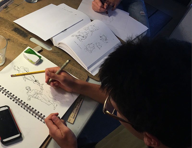 Youth sketcher, Casey, enjoys applying principles of accurate proportions as he sketches the movement of a comic figure.